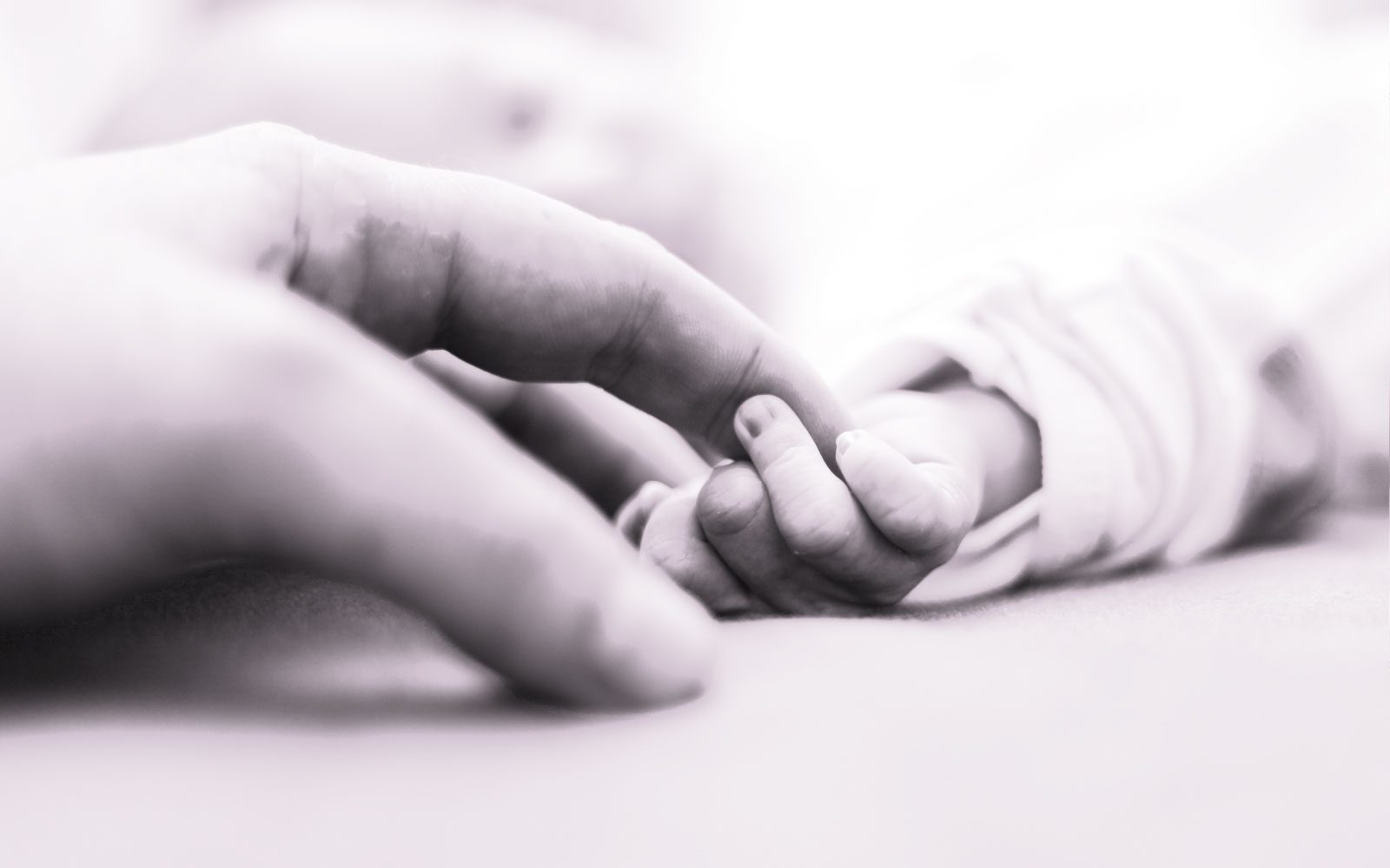 black and white baby and mother holding hands