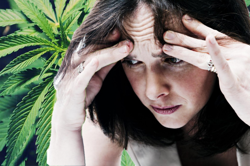 woman holding head looking anxious on cannabis leaf background