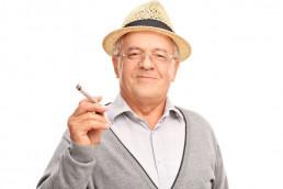 Happy smiling old man enjoying marijuana cigarette