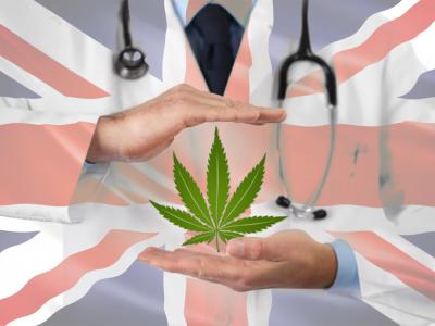 Scientist wearing white coat holding cannabis leaf on British flag background