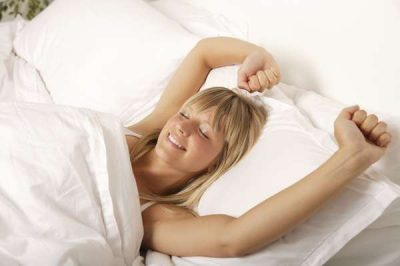 White blonde woman smiling with arms stretched out in bed, smiling as waking up