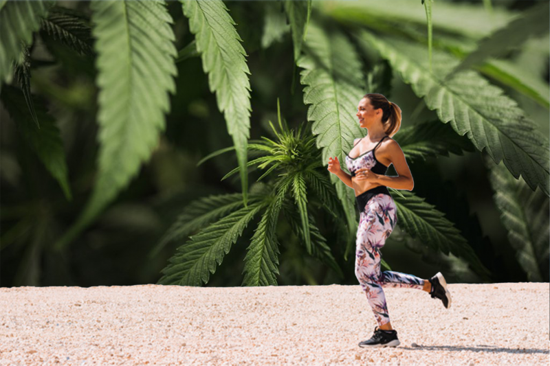 Smiling woman wearing sports clothes running on a beach with cannabis leaves as background