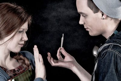 Male teenager using cannabis, offering female teenager cannabis joint, who refuses